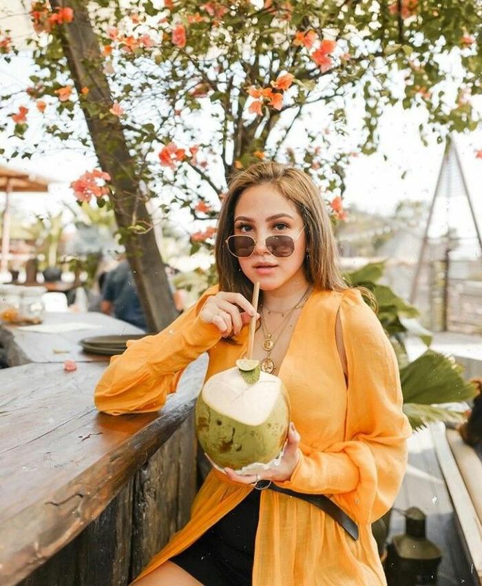 Berfoto dengan baju oranye dan kacamata hitam. Mantan pemain sinetron Benci Bilang Cinta ini pun terlihat asyik menikmati kelapa muda. Foto: Instagram @paolatambunann