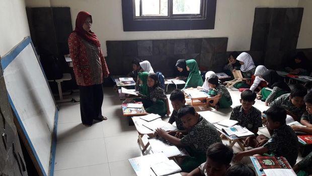 Guru mengajar dengan papan tulis yang disandarkan di dinding.