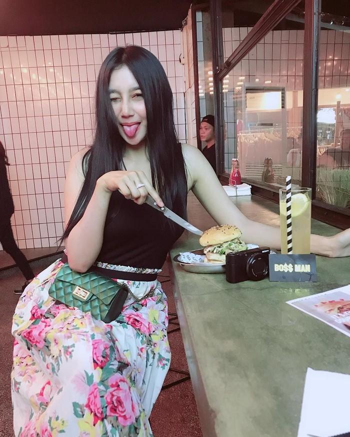 Makan burger dengan segelas minuman segar, Pamela tampil cantik dan modis saat makan di restoran yang Instagrammable. Foto: Instagram @pamelaaasafitriduoserigala