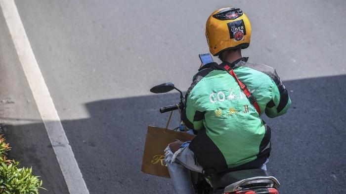 Ilustrasi driver ojol melihat GPS saat berkendara. (Foto: Antara Foto/Hafidz Mubarak A)
