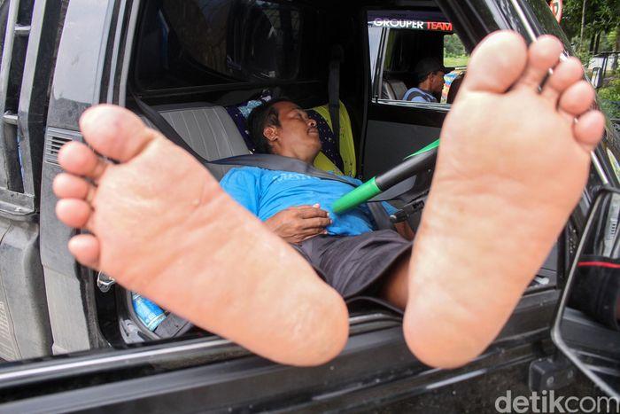 Seorang sopir truk tertidur di mobilnya saat beristirahat di rest area KM 86 Tol Trans Jawa jalur Jakarta-Semarang.