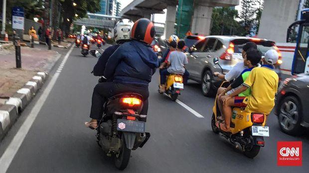 Pengguna sepeda listrik Migo tidak menggunakan helm dan mengendarai sepeda di jalan raya.