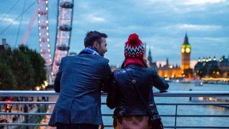 Back view of tourists couple wearing winter clothes looking at Big Ben and London Eye in the evening.