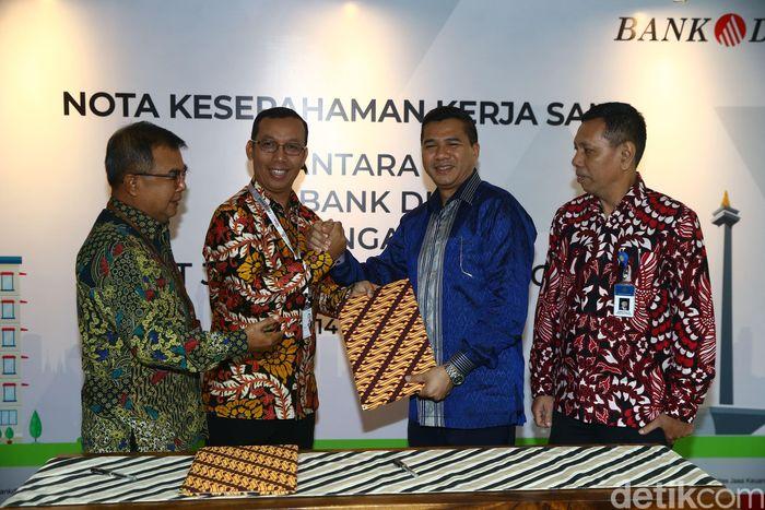 Direktur keuangan Bank DKI Sigit Prastowo dan Dirut Jakarta Tourisindo Geraard Jeffrey Z Rantung, disaksikan Dirut Bank DKI Wahyu Widodo saat melakukan penandatangan kerjasama di Kantor Bank DKI, Jakarta (14/2/2019).