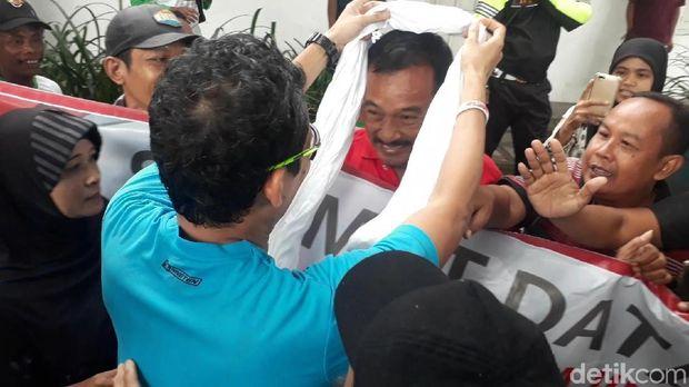Sandiaga mengalungkan serban putih ke warga Bojonegoro yang membawa poster dukungan untuk Jokowi.