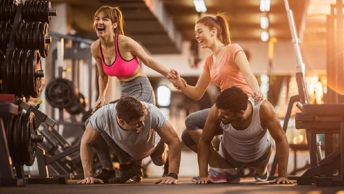 Cheerful men doing push-ups in a health club while women are sitting on their backs and laughing. Focus is on men.