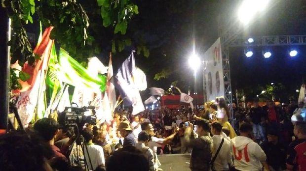 Pendukung Jokowi-Ma'ruf mengibarkan bendera di lokasi nobar di Parkir Timur Senayan.