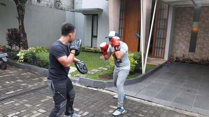 Tommy (kaos abu-abu) latihan kickboxing satu kali seminggu bersama pelatih yang datang ke rumahnya. (dok. pribadi Tommy Tjokro)