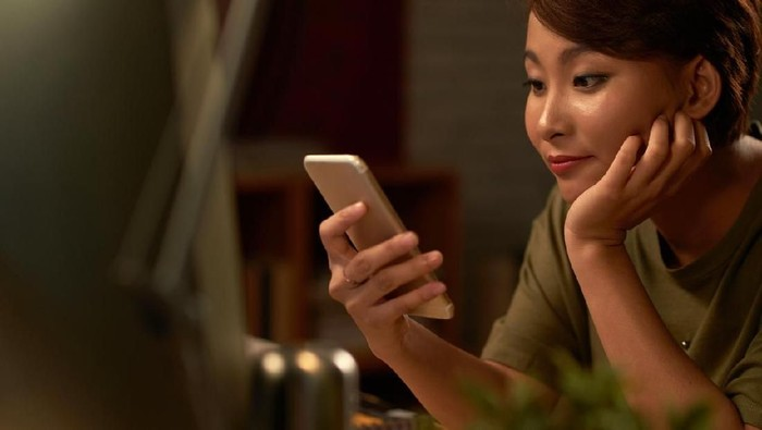 Closeup of thoughtful young Asian woman holding mobile phone and surfing Internet. Attractive student taking selfie at cafe. Communication and work balance concept