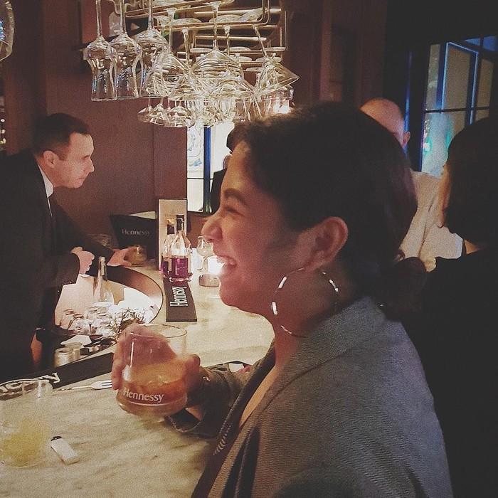 Mengenakan baju abu-abu, Nadien terlihat tengah memegang minuman coktail dingin. Foto: Instagram@nadinemmanuella
