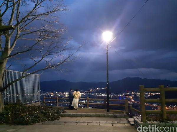 Sepasang insan maju ke pagar pembatas sambil bergandengan. Mereka menikmati denyut lampu kota sambil memadu kasih. Ah, sungguh romantis.. (Bonauli/detikTravel)