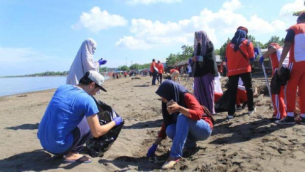 Para remaja di Makassar bersih-bersih sampah di pantai.