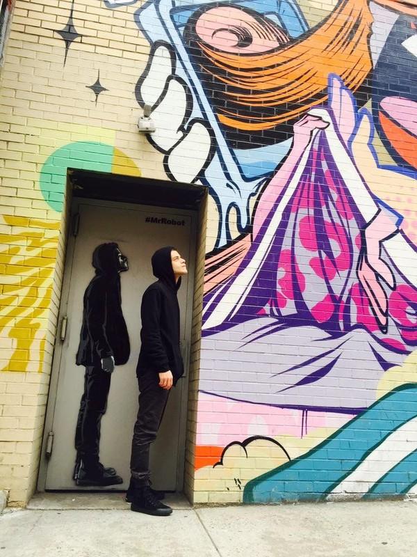 Rami berfoto di salah satu mural Mr Robot, di jalanan New York. Mr Robot adalah film yang dibintanginya. (@ItsRamiMalek/Twitter)