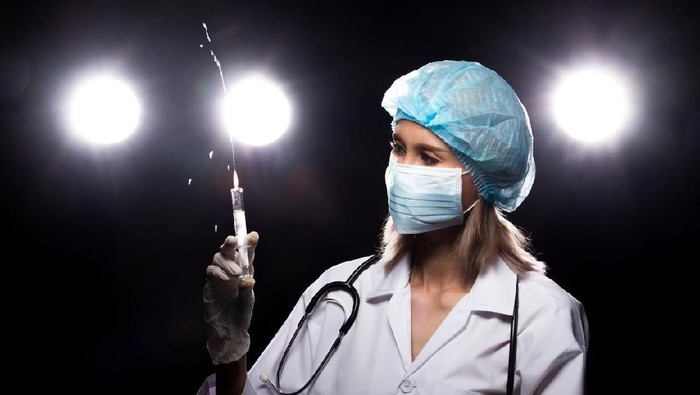 Asian Beautiful Doctor Nurse woman in uniform with stethoscope, rubber gloves, mask check syringe injection, portrait , studio lighting dark background four back light flare silhouette copy space