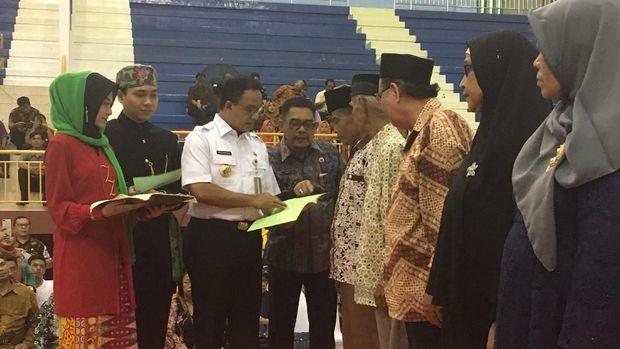 Gubernur DKI Anies Baswedan secara simbolik membagikan sertifikat tanah ke warga Cipayung dan Makasar, Jakarta Timur.