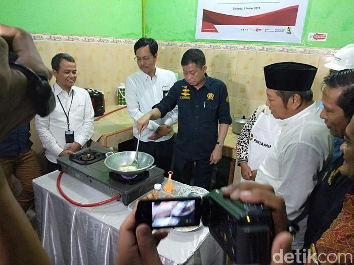 Foto: Menteri ESDM Ignasius Jonan bersama bupati Sidoarjo Saiful Ilah memasak di rumah Jumaiyah (Suparno Nodhor/detikcom)