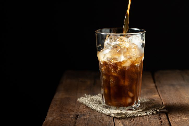 Ice coffee in a tall glass over and coffee beans on a old rustic wooden table. Cold summer drink on a dark background with copy space. The process of pouring drink from a coffee pot into a glass.