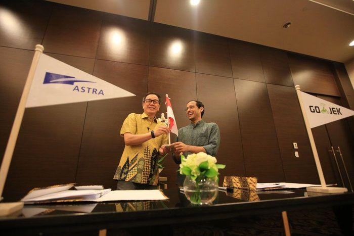 Presiden Direktur PT Astra International Tbk Prijono Sugiarto (kiri) dan Chief Executive Officer & Founder Go-Jek Nadiem Makarim berbincang seusai penandatanganan kesepakatan pembentukan perusahaan patungan (joint venture/JV) untuk mendorong pengembangan bisnis ride hailing roda empat di Jakarta, Senin (4/3). Pool/Astra.