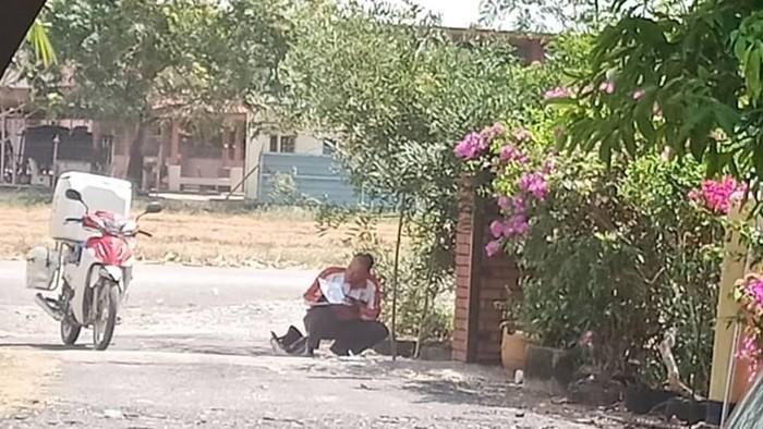 Potret tukang pos berteduh viral. Foto: Facebook