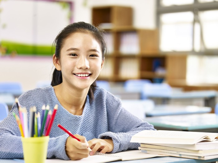 happy asian elementary school student studying in classroom looking at camera smiling,