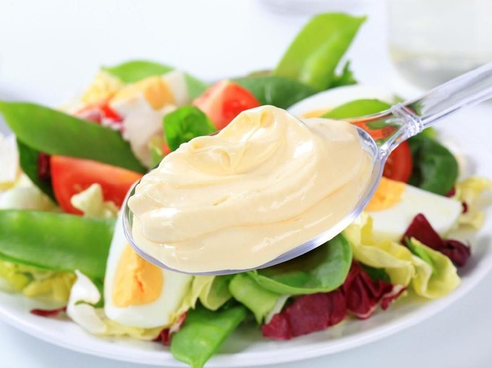 Homemade mayonnaise in bowl with eggs and spice on wooden background