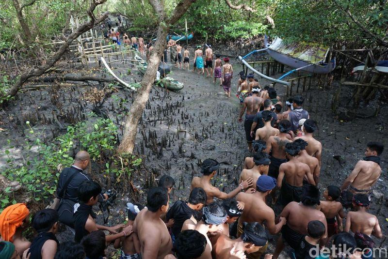 Sehari setelah Nyepi, umat Hindu di Bali merayakan Hari Ngembak Geni. Salah satu tradisi unik di Desa Adat Kedonganan, Badung, Bali yakni Mebuug Buugan atau ritual mandi lumpur. (Aditya Mardiastuti/detikTravel)