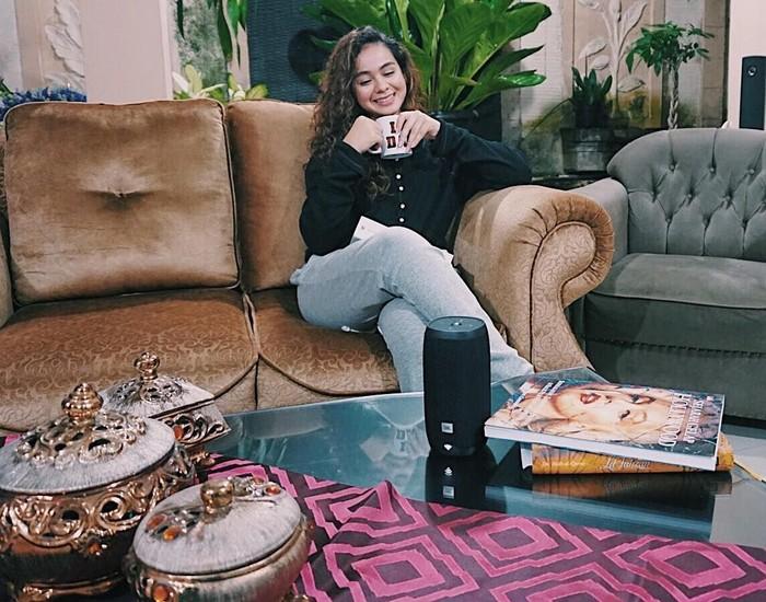 Wanita berambut keriting ini terlihat sedang menikmati teh hangat. Tentunya sambil duduk santai di rumah. Foto: Instagram@sahilahisyam