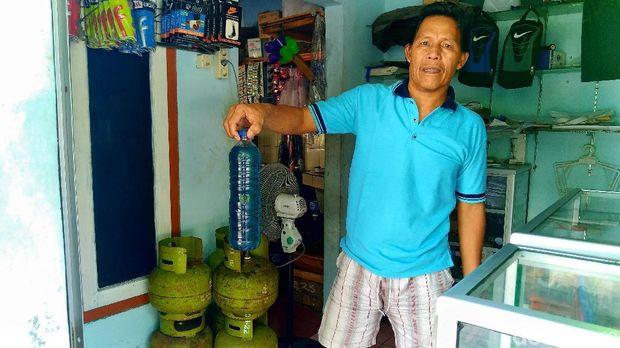 Tomi pemilik Warung Rembulan Pulau Pramuka menunjukkan pertalite yang dijualnya.