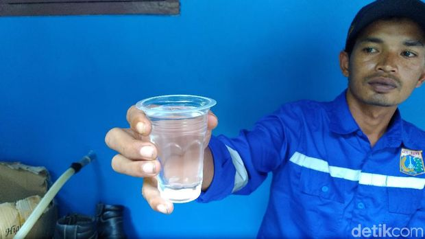 Suwarjo menyodorkan air minum produk instalasi BWRO di Pulau Pramuka.