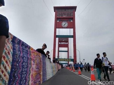 Jokowi Hadiri Pemecahan Rekor Muri Kain Jumputan 1,1 KM di Jembatan Ampera