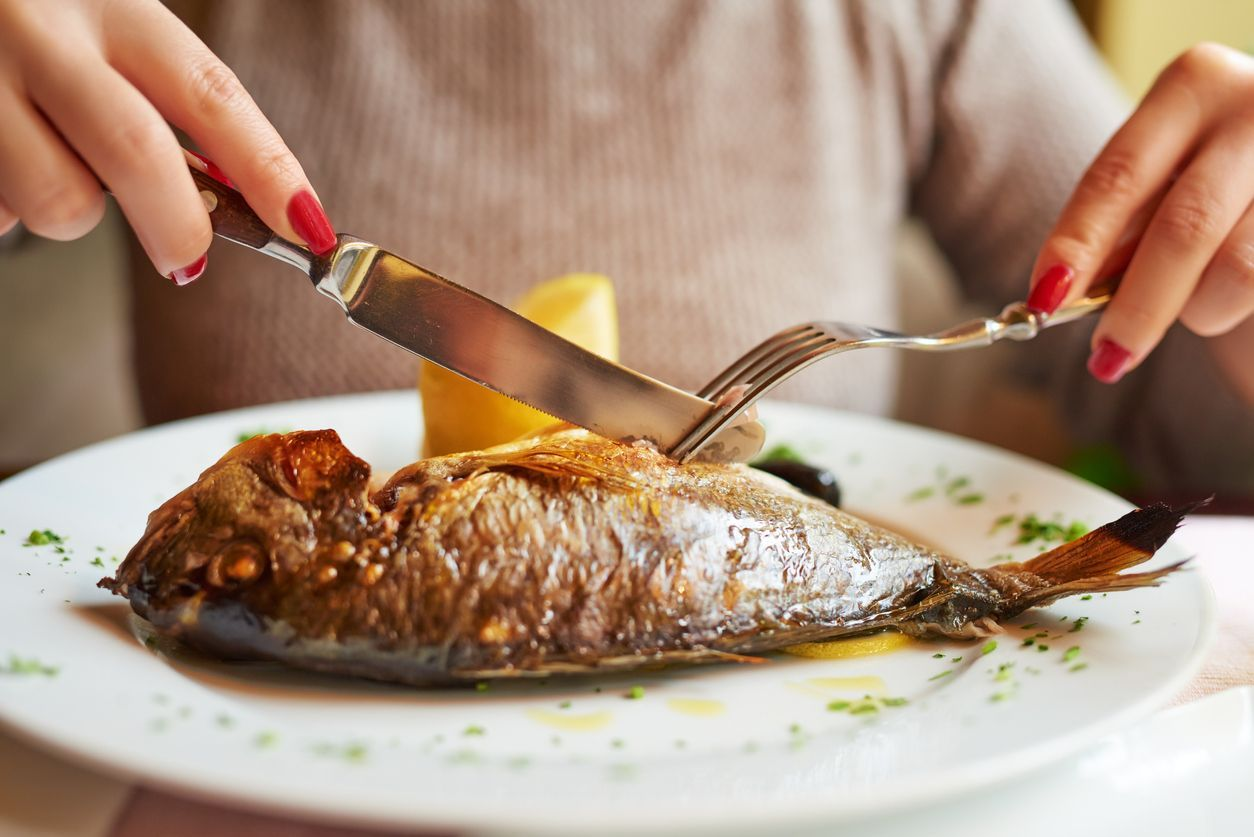 woman hands eating fish at restaurant, having her lunch.