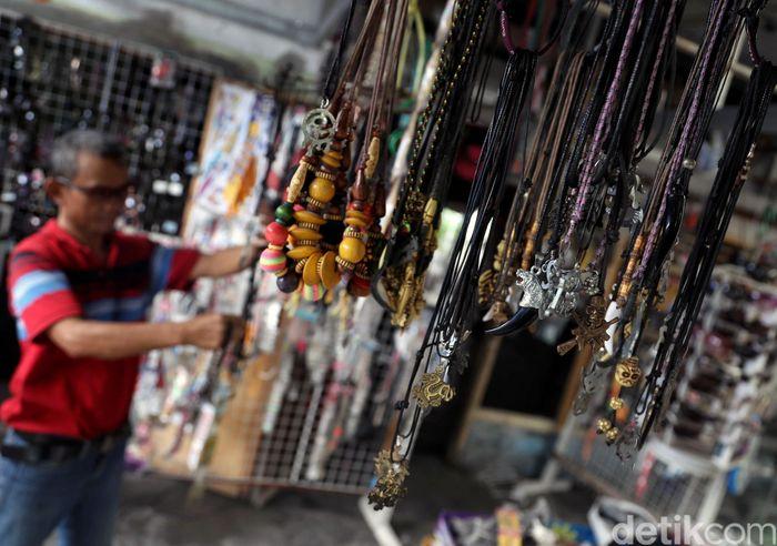 Seorang pedagang memperlihatkan barang dagangannya berupa gelang, kalung dan pernak-pernik lainnya di Pulau Harapan, Kepulauan Seribu.