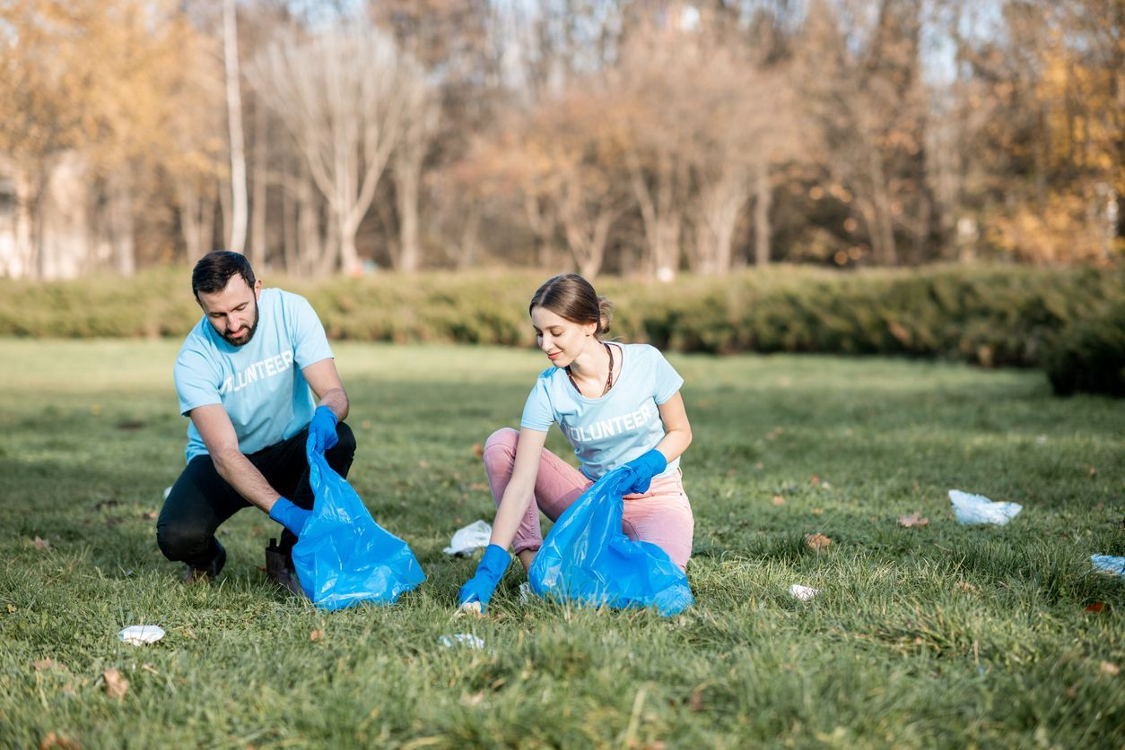 Happy man and woman volunteers dressed in blue t-shirts cleaning public garden from plastic rubbish into the bags
