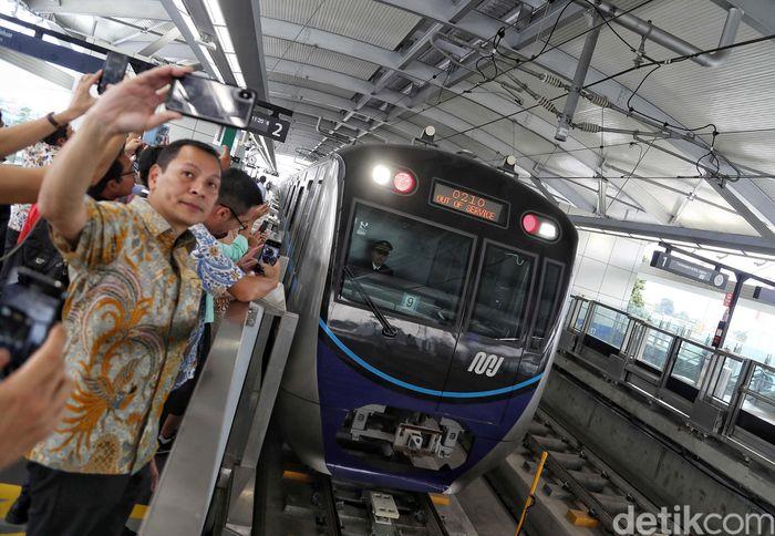Beberapa warga berselfie dengan latar belakang kedatangan kereta MRT.