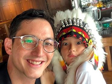Papa Mike mengajak Kenzou ke Surabaya. Wah si Kenzou pakai topi Indian yang unik banget. Jadi makin ganteng ya, Bun. (Foto: Instagram: @mike_lewis)