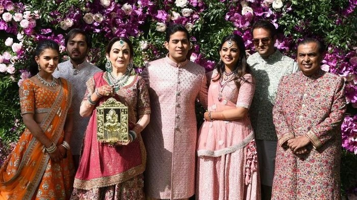 Akash Ambani (C), son of Indian businessman Mukesh Ambani (R) and businesswoman Nita Ambani (3rd L), their daughter Isha Ambani (3rd R) and her husband Anand Piramal (2nd R), son of Indian billionaire industrialist Ajay Piramal (not pictured), pose during the wedding ceremony of Akash Ambani in Mumbai on March 9, 2019. (Photo by SUJIT JAISWAL / AFP)