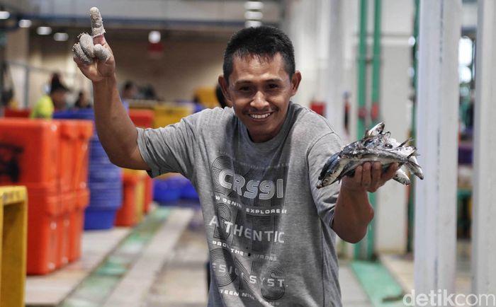 Seorang pedagang menunjukan ikan yang akan dijualnya di Pasar Ikan Modern Muara Baru.