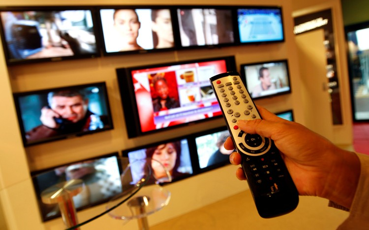 FILE PHOTO: A visitor uses a remote control as she looks at television programmes during the annual MIPCOM television programme market in Cannes, southeastern France, October 4, 2010. REUTERS/Eric Gaillard/File Photo