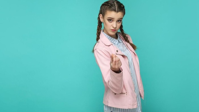 money gesture. portrait of beautiful cute girl standing with makeup and brown pigtail hairstyle in striped light blue shirt pink jacket. indoor, studio shot isolated on blue or green background.