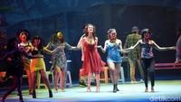 Dari atas panggung teater, ia menggunakan gaun selutut terbuka berwarna merah menyala. Foto: (Noel/detikhot)