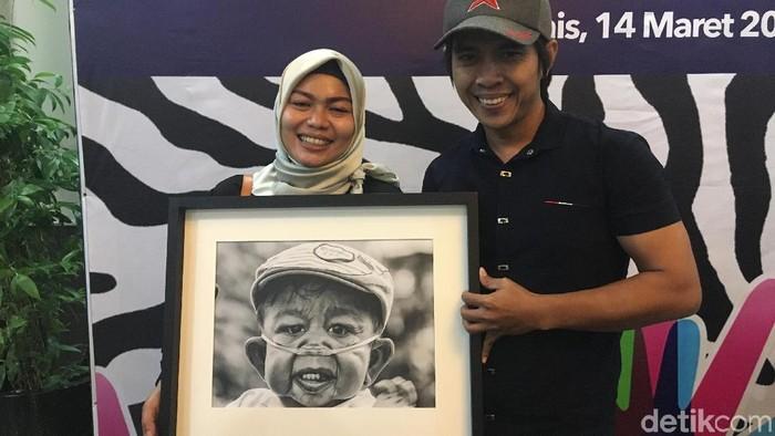 Winda dan Sanudin, berpose bersama foto Raka, pengidap Cutis Laxa Syndrome. Foto: Frieda Isyana Putri/detikHealth