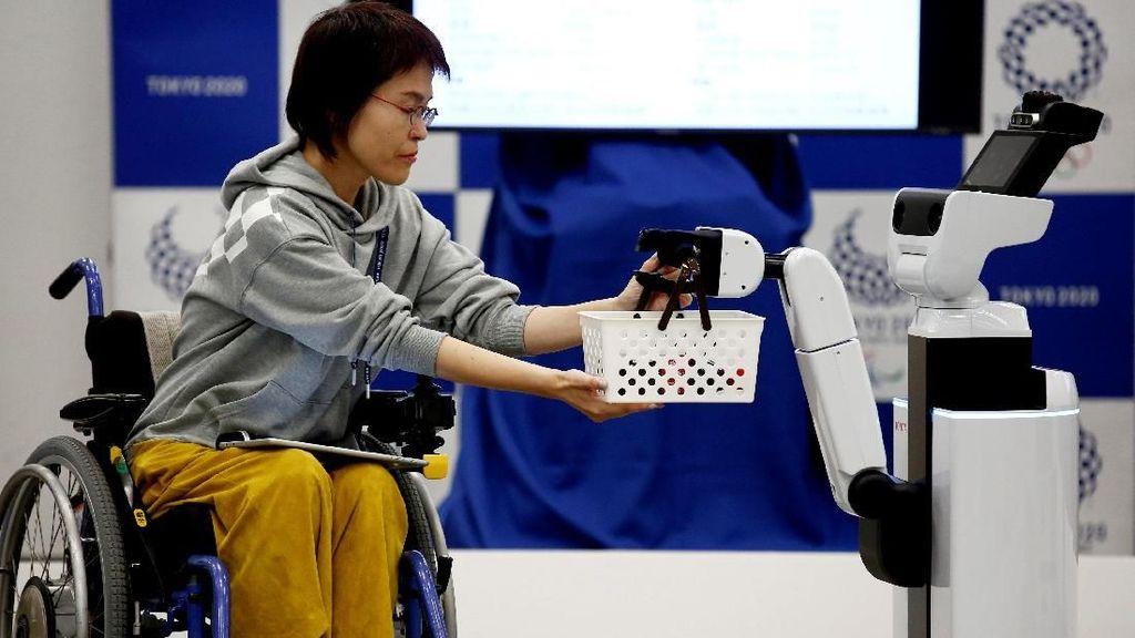 Aksi robot HSR mengantarkan keranjang ke seorang perempuan di kursi roda. (Foto: REUTERS/Kim Kyung-hoon)