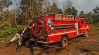 Petugas gabungan dari Pemadam Kebakaran dan Badan Penanggulangan Bencana Daerah (BPBD) Kota Pekanbaru berusaha mengeluarkan mobil pemadam yang terpuruk ketika akan memadamkan kebakaran lahan gambut di Pekanbaru, Riau, Senin (18/3/2019). ANTARA FOTO/Rony Muharrman.