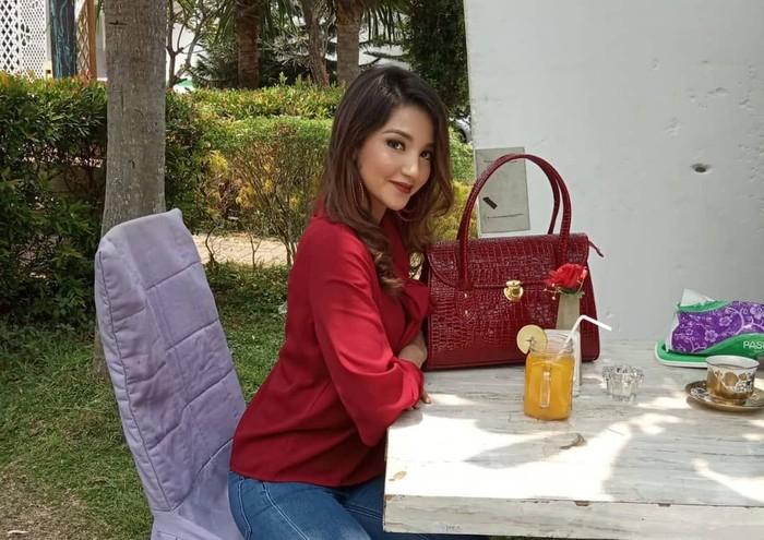 Mengenakan pakaian merah, Tasnia terlihat sedang duduk santai menikmati segelas jus jeruk yang dingin. Mantan istri Atalarik Syah ini kini sedang memperjuangkan hak asuh anak. Foto: Instagram@tsaniamarwa54