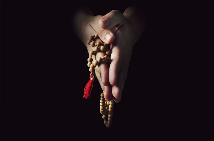 Hands folded in prayer on a black isolated background. The priest in prayer. Rosary in the hands of men