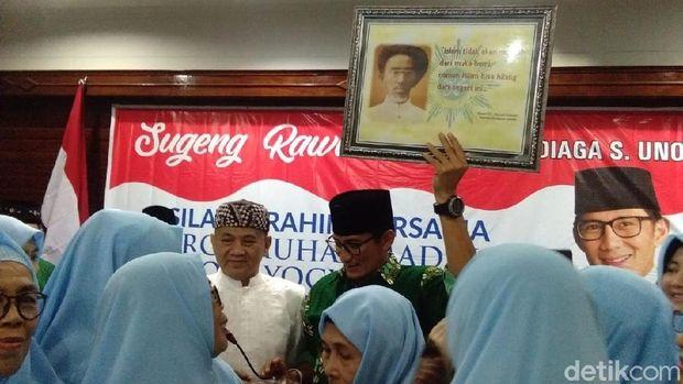 Sandiaga Uno menunjukkan isi bingkisan dari keluarga KH Ahmad Dahlan.