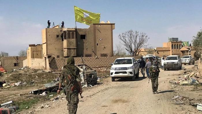 Bendera SDF dikibarkan di Barghouz, Suriah usai ISIS dinyatakan kalah total (REUTERS/Stringer)