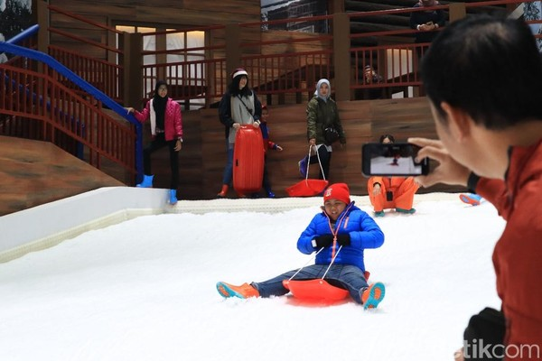 Seorang ayah memotret anaknya di seluncuran salju. Trans Snow World cocok banget untuk liburan keluarga (Randy/detikcom)