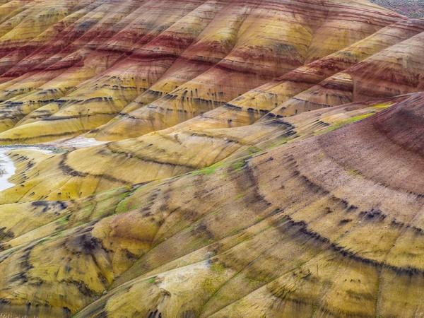 Permukaan perbukitan ini terlihat memiliki garis-garis, dengan warna kemerahan, coklat, oranye, kuning hingga kehitaman (iStock)