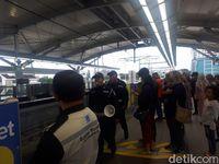 Petugas yang mengimbau penumpang untuk berada di belakang garis kuning (Shinta/detikcom)